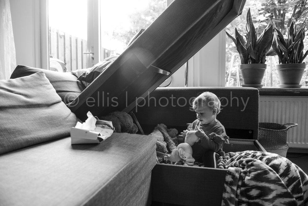 Kleuter is in haar speelbank ongestoord aan het spelen met haar knuffel. Ongedwongen familie daily life documentaire. Familie reportage door Ellis Peeters Photography. Zwart wit portret fotografie.