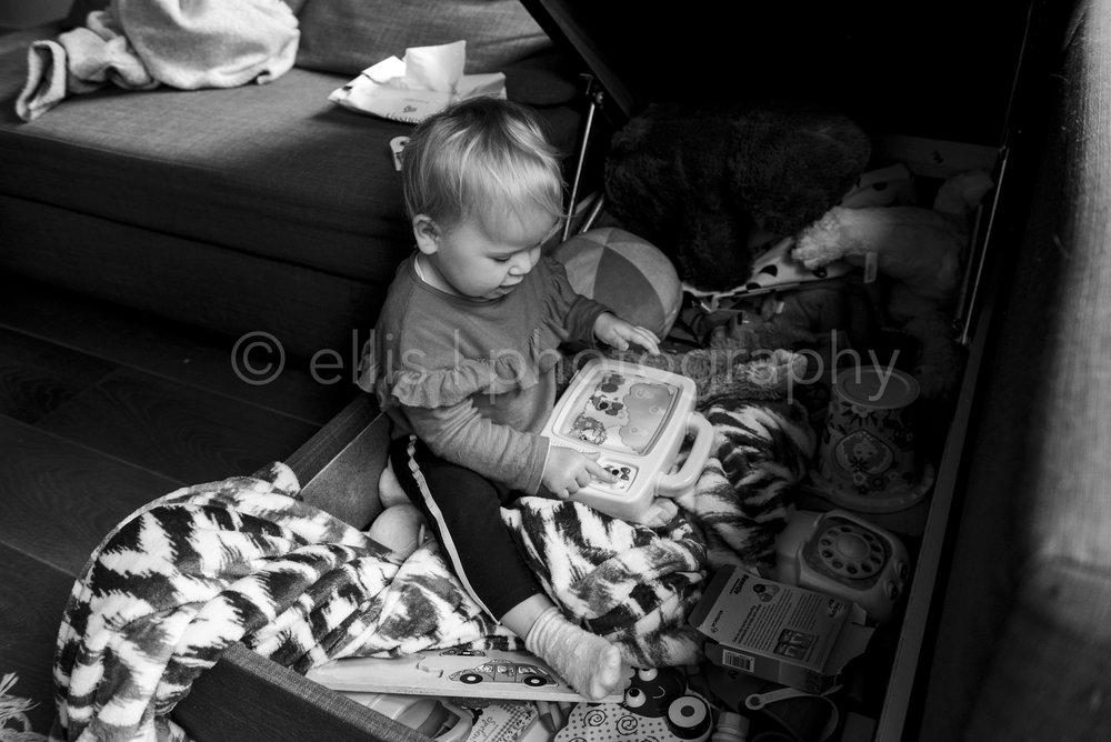 Peuter is met haar woezel en pip speelgoed in haar speelbank aan het spelen. Zwart wit daily life fotografie. Familie shoot in het dagelijks leven.