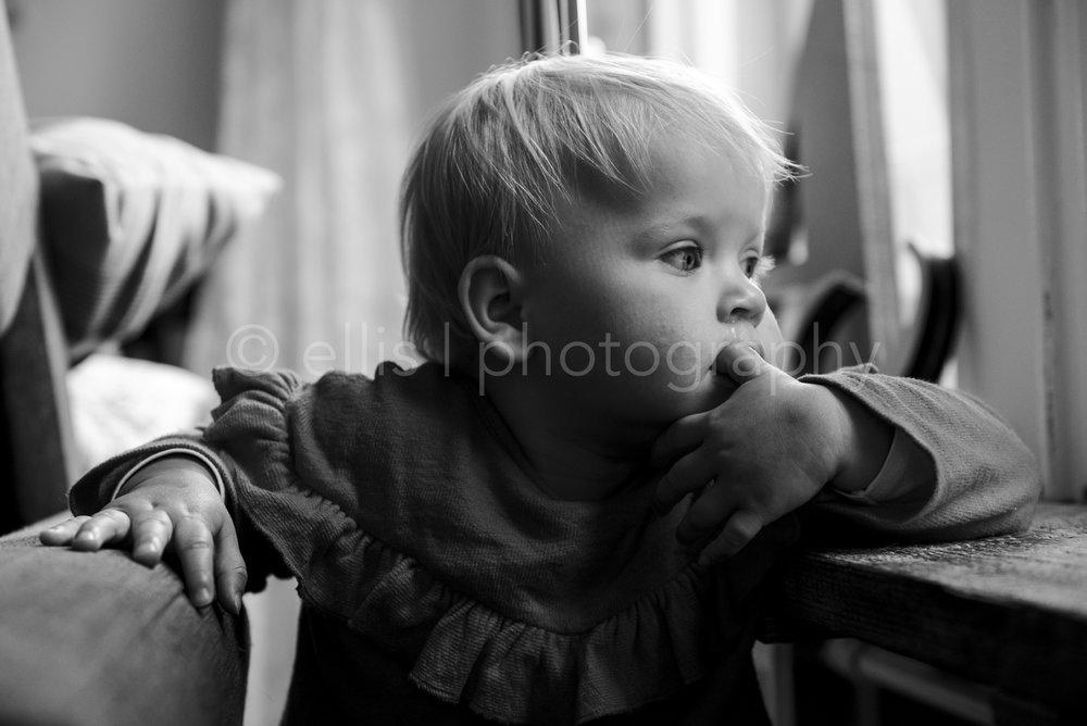 Dreamy baby. Looking outside through the window. Black and white daily photography by Ellis Peeters. Dromerige dreumes die naar buiten kijken. Zwart wit familie fotografie.
