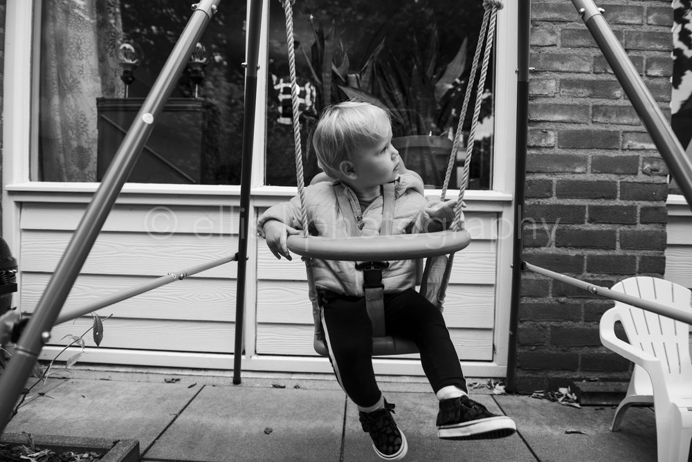 Young girl in a swing. Not paying attention. Daily life Black and white photo by Ellis photography. Klein meisje in een schommel. In haar eigen wereldje. Zwart wit daily life fotografie.