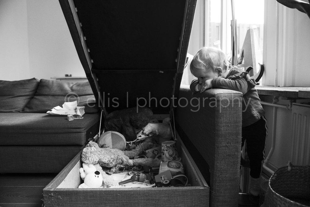 Little girl looking at her toys. Klein meisje kijkt naar al haar speelgoed. Familie fotografie. Family photography. Daily life black and white. Zwart wit.