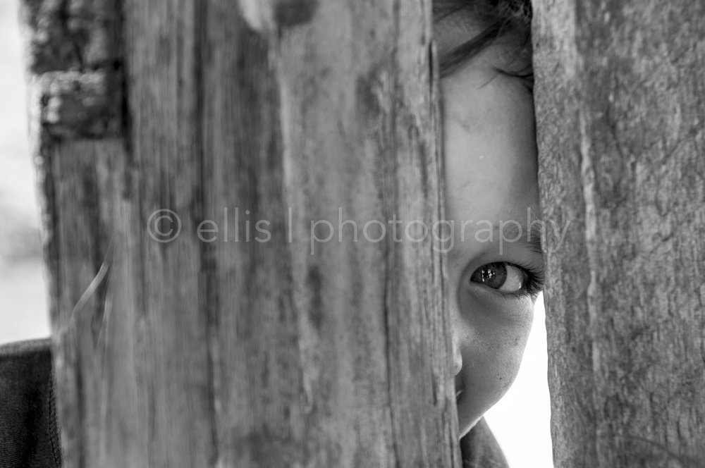 Little cute boy is looking carefully through a wooden fence. His beautiful big eye pops out between the wood. He looks full of life, curious, innocent and cute.This black and white photo is part of the Portraits of a Romanian Family series, made by Ellis Peeters Photography. Daily life photography