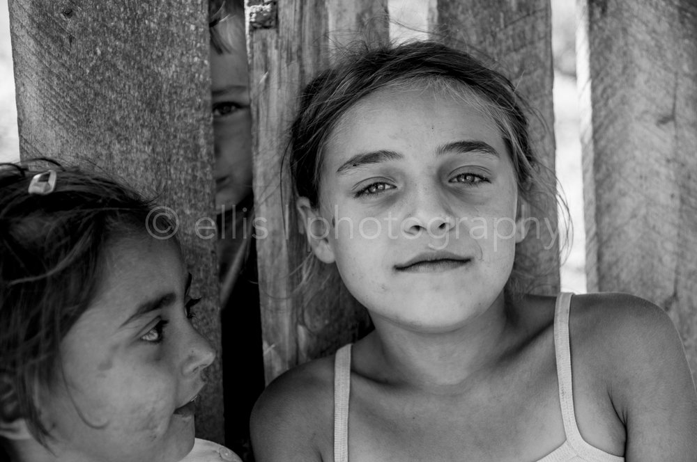 Young beautiful gipsy girl looks confident and in total peace in the camera. She doesn't bother me taking pictures of them. Younger sister looks to big sister and the younger brothers stands safe behind the fence, looking through the wood. Part of the series 'Portraits of a Romanian Family'.