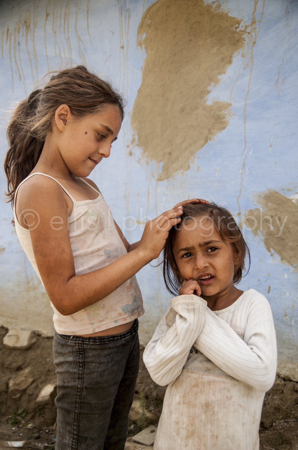 Young Romanian gipsy girl is fixing the hair of her younger sister, because their mother has no time. They are totally in their own world. Not minding me taking pictures. Daily life photography taken by Ellis Peeters photography.