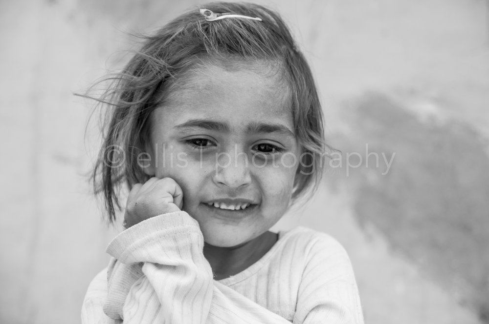 Portrait of a Cute little Romanian gipsy girl. Black and white picture. Totally in her own world. Part of the series Portrait of a Romanian Family by Ellis Peeters Photography.