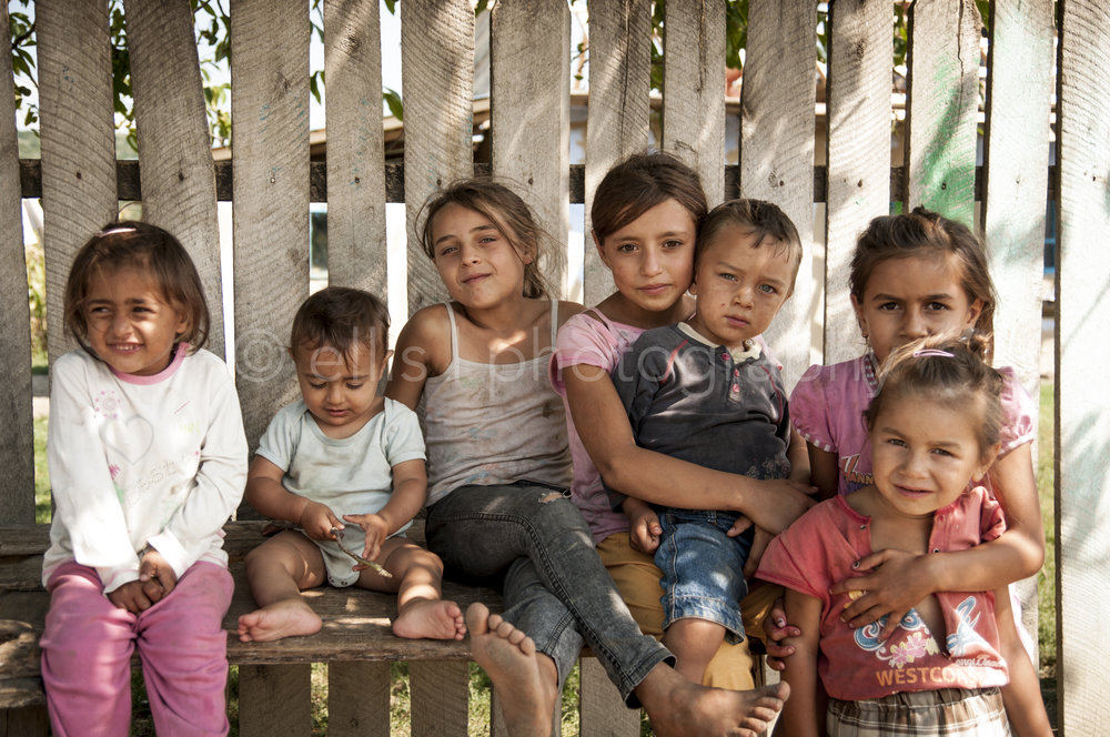 Young cute gipsy kids, family and friends sitting on a bench against a wooden fence. Some in their own world, some looking into the lens. Portraits of a Romanian Family.
