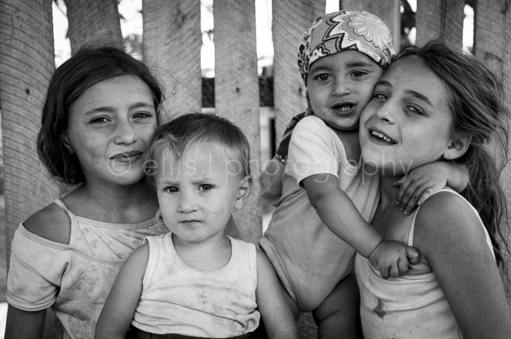 Black and white photo of some gipsy kids / friends and neighbours in a gipsy area of Romania. Ellis Peeters Photography, daily life photography