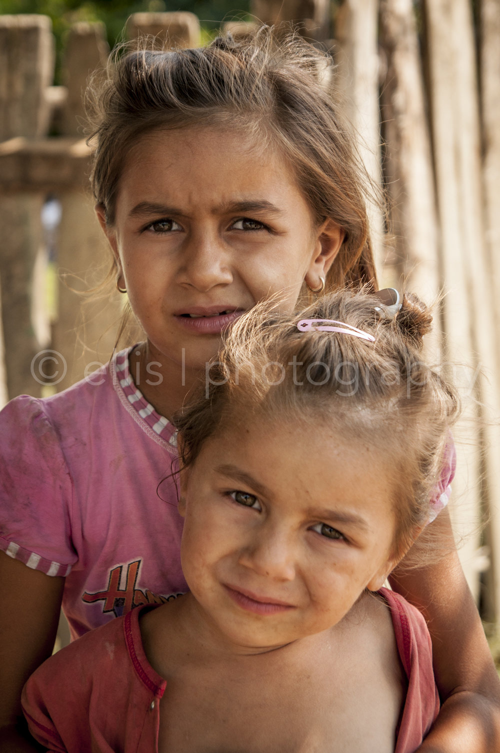 Two young gipsy sisters. Youngest sits on the lab of the older sister. Portraits of a Romanian Family. Ellis Photography - daily life photography