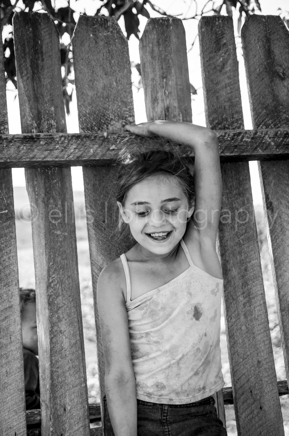 Young dirty gipsy girl stands against a wooden fence. Not looking into the camera but has a big beautiful smile on her face! Beautiful portrait young girl. Part of the series Portraits of a Romanian Family. Made by Ellis Photography