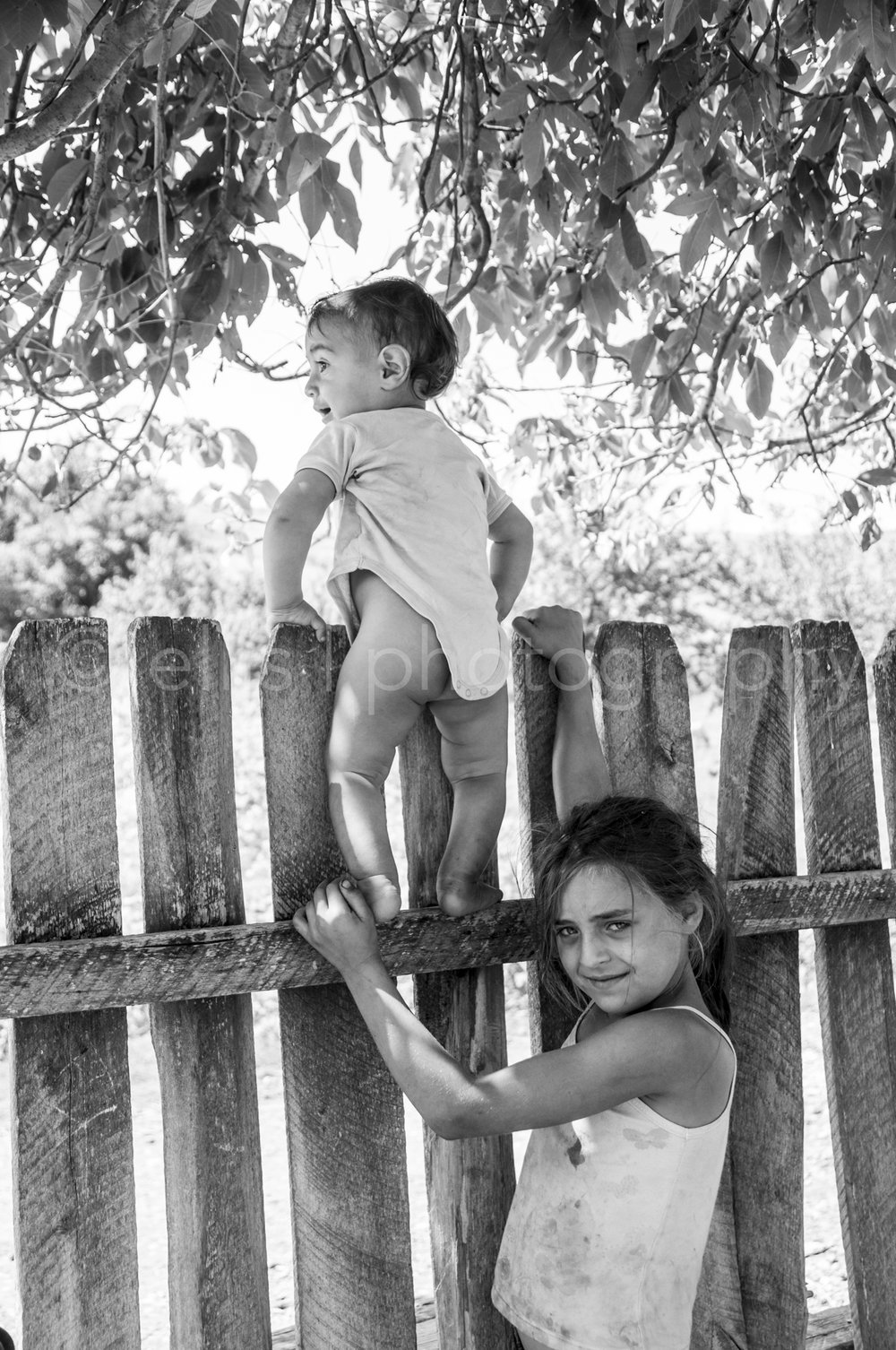 Young Romanian gipsy girl watches over her baby brother who is standing on the wooden fence. Portraits of a Romanian Family. Made by daily life photographer Ellis Photography.