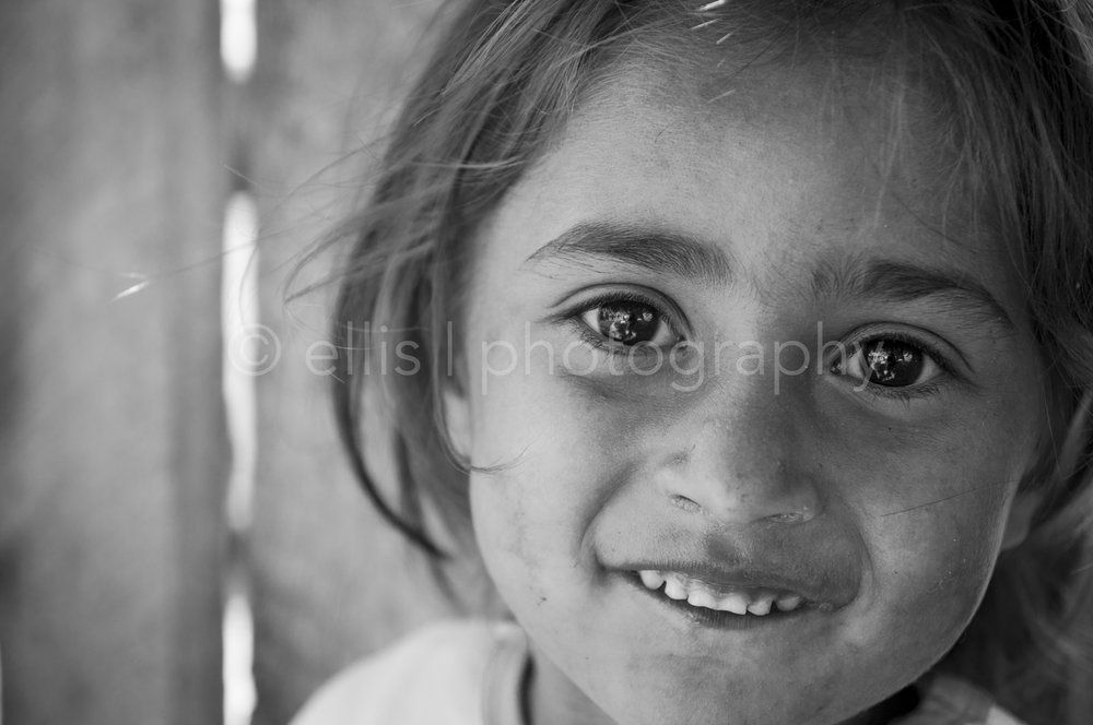 """Black and white portrait of a young cute gipsy girl full of energy. Big eyes look playful in the camera. Ellis Photography and Portraits of a Romanian Family""""."""