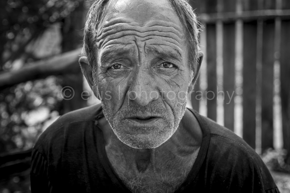 Romanian gipsy grandpa. Black and white portrait of an old man. Little bit a white beard. Part of the series Portraits of a Romanian Family by Ellis Photography