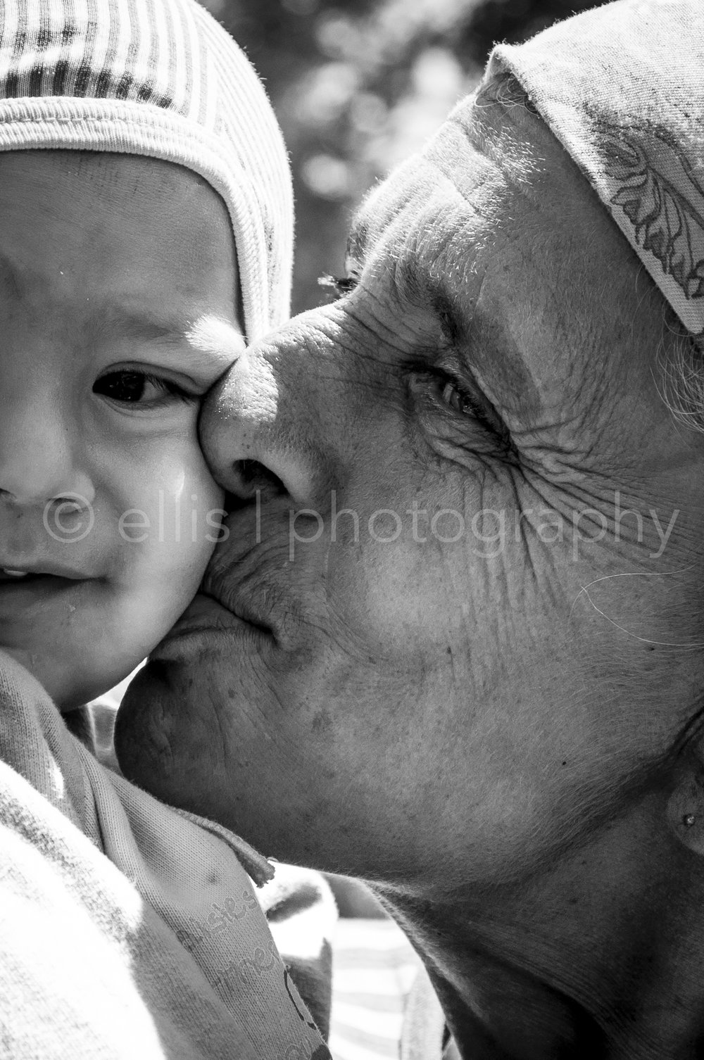 close-up portrait of an gipsy grandma with her grandchild. Grandma is giving her grandchild a kiss on the cheek. Ellis Photography