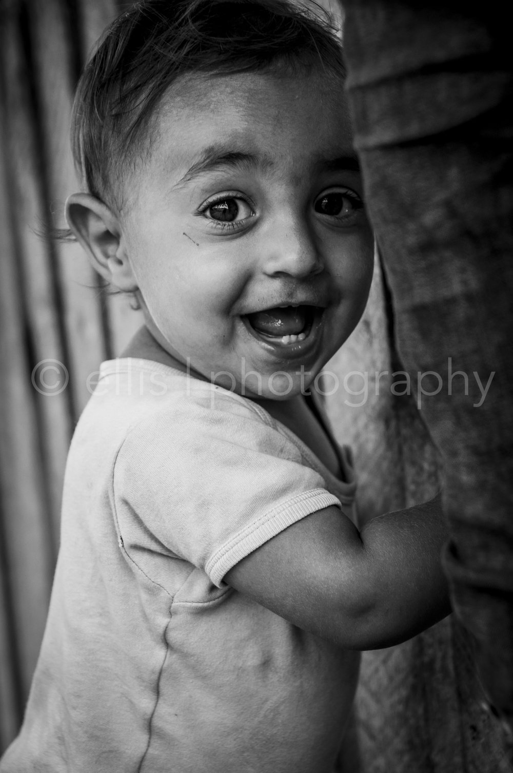 Gipsy baby boy holding on to the wooden fence. Looking happy in the camera. Big smile and big eyes. Black and white daily life Photography.