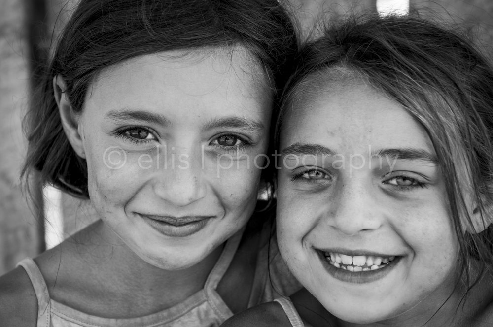 Two girls, romanian gipsy friends. Big eyes en beautiful smiles. Black and white photography by Ellis Photography