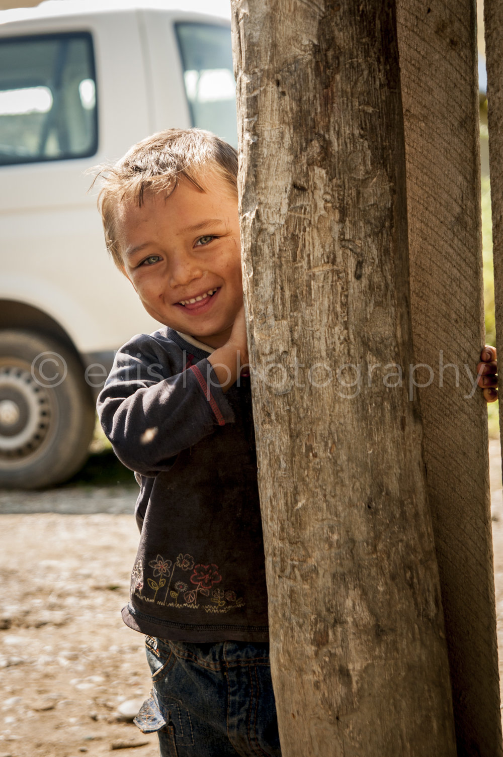 Young gipsy boy is coming out of his safe place, behind the fence. Curious for me and the camera. Looks super sweet and cute into the camera. Daily life photographer Ellis Photography - Portraits of a Romanian family.