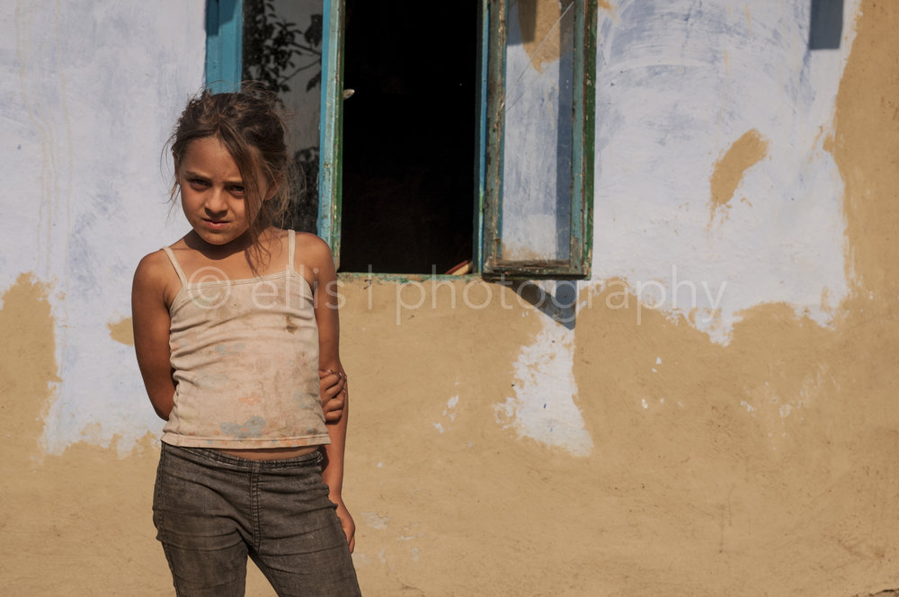 Young girl stands in front of her house. Gipsy daily life photography of a Romanian family.