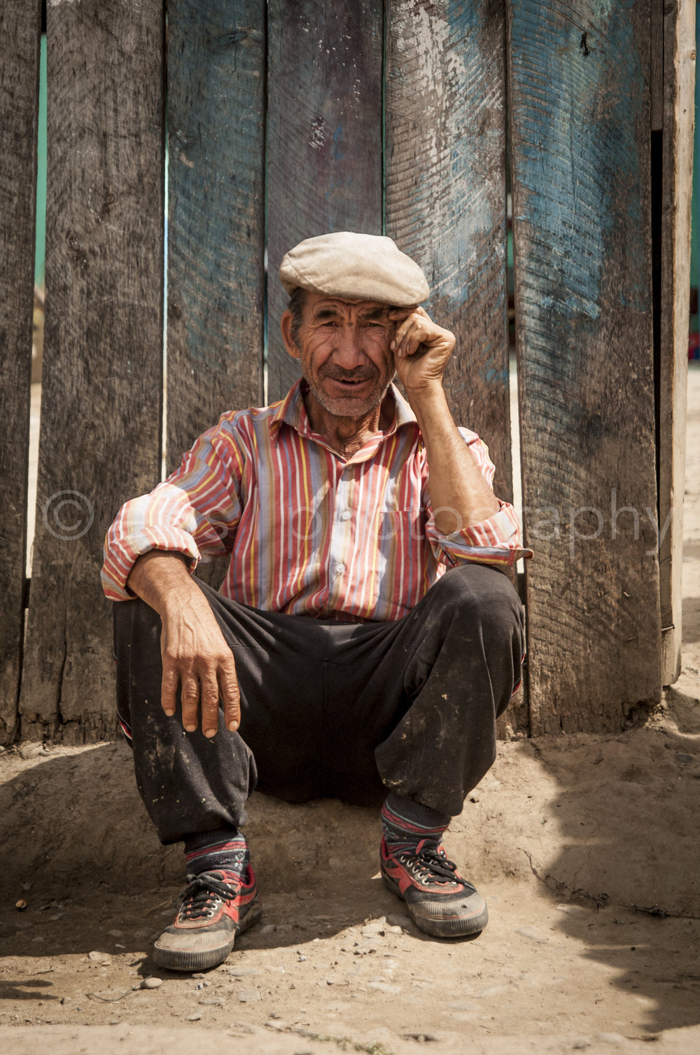 Old man sitting against a fence, along side of the road, chilling. Wearing a head and a colourful blouse. Portraits of a Romanian Family by Ellis Photography