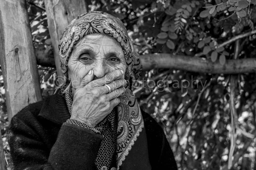 Daily life black and white photo of an old lady, sitting on the side of the road. Holding her old wrinkled hands in front of her mouth. Being a bit shy to be photography. Old wrinkled face. Ellis Peeters photography