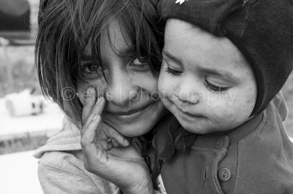 Gipsy brother and sister. Sister carries her younger brother. Cute Romanian faces. Portraits of a Romanian family.