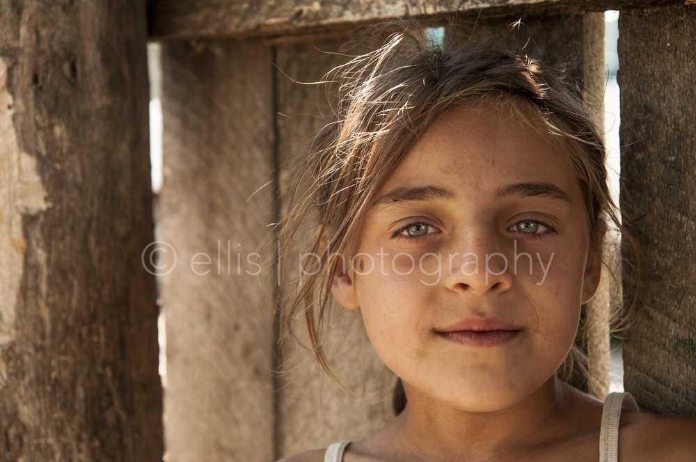 Portrait of a beautiful Romanian young gipsy girl. Looks confident and in ease in the camera. Beautiful green eyes. Portraits of a Romanian Family , daily life photography taken by Ellis Photography.
