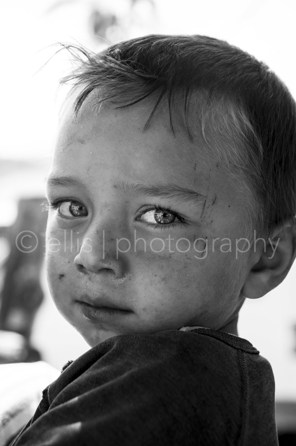 Very cute little boy. Portrait of a Romanian boy with beautiful big eyes looking into the camera. Although he is pretty dirty, his eyes get all the attention. Black and white photography by Ellis Peeters Photography for Portraits of a Romanian Family - daily life photography.