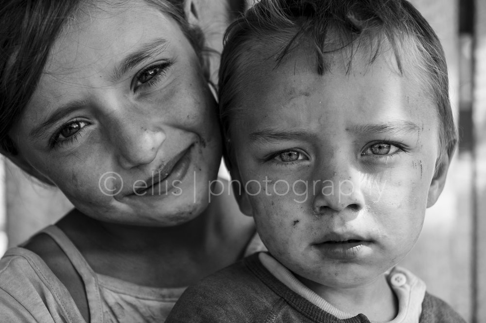 Two beautiful gipsy kids with beautiful eyes. Black and white photography by Ellis Peeters Photography. Portraits of a Romanian Family.