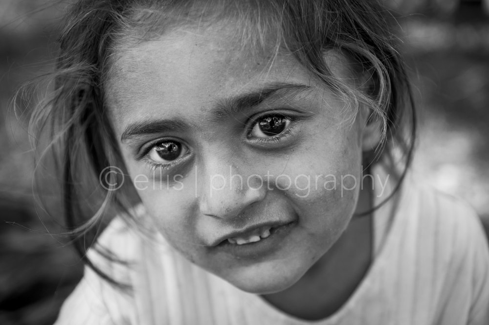 Black and white portrait of a young cute gipsy girl full of energy. Big eyes look playful in the camera. Ellis Peeters