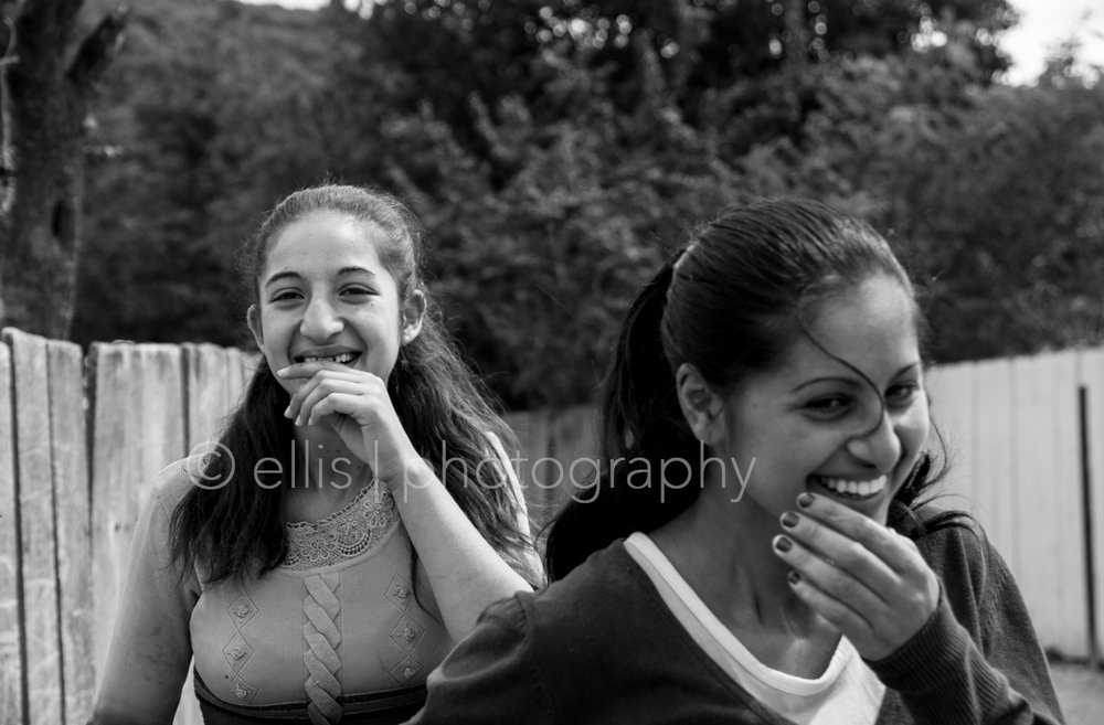 Two shy Romanian gipsy women. Laughing and holding their hands in front of their mouths.