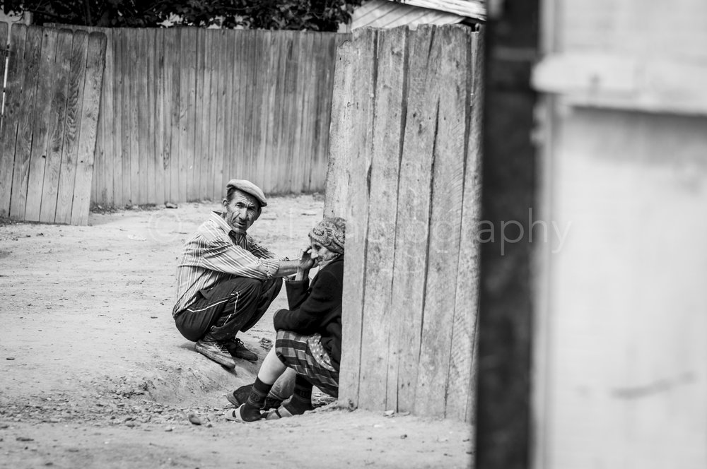 Old gipsy people, grandma and grandpa, sitting at the side of the road, relaxing together. Lot of wooden fences.