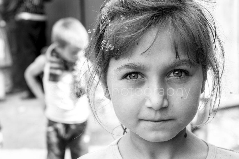 This Romanian girl was playing with the bubble blow. We had a short moment of connection, so I could make a beautiful black and white portrait of her. I love how her eyes speak and her not being afraid to look in the camera. Daily life by Ellis Photography.