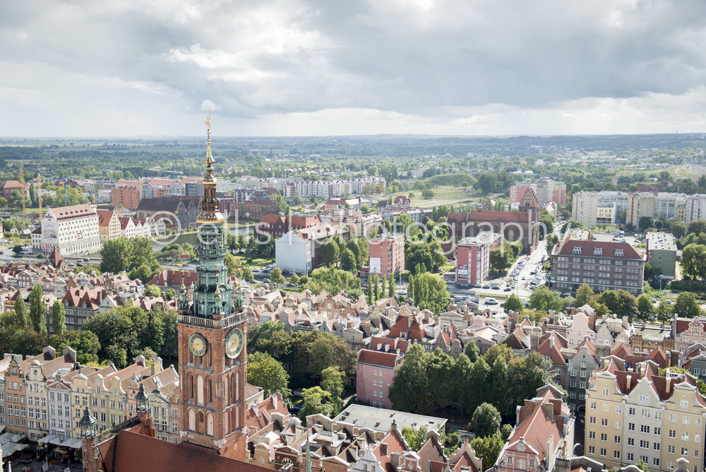 Beautiful view from the St. Mary's church of Gdansk, Poland. Houses with a Dutch design aligned.Clouds lay like a blanket above the city of Gdansk. The church tower peaks out.