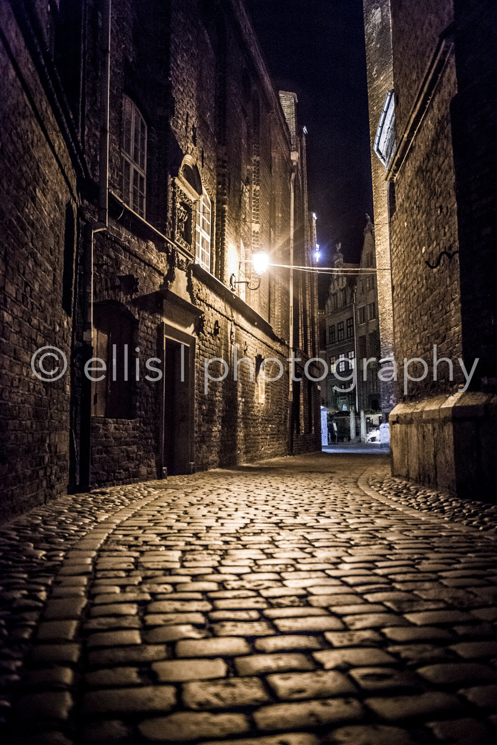 Night photography in Gdansk.While wandering around and exploring Gdansk by night, we walked through this narrow street with beautiful light and a brick street. I just had to take a picture. Ellis Photography, who likes to travel the world,