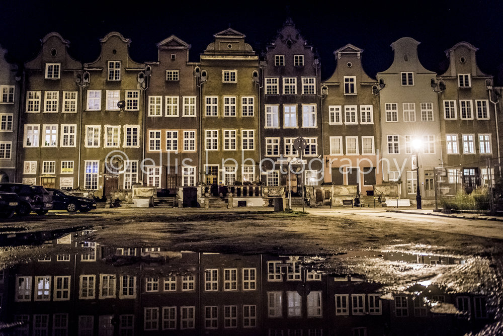 Traveling through Europe, these are houses in Gdansk, designed by a dutch architect. Reflection in a puddle of water. Streetlights make it a cosy, warm photograph. Photo taken by Ellis Photography
