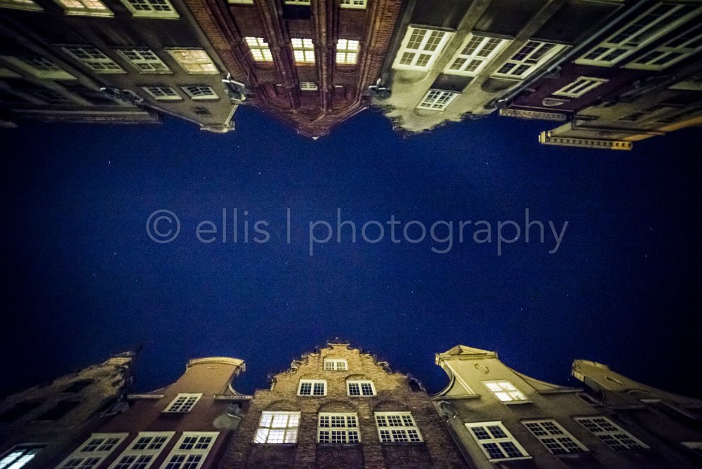 Photograph looking up in the streets of Gdansk, by night. Dark blue sky with the rooftops of the houses designed by a Dutch architect. Ellis Photography