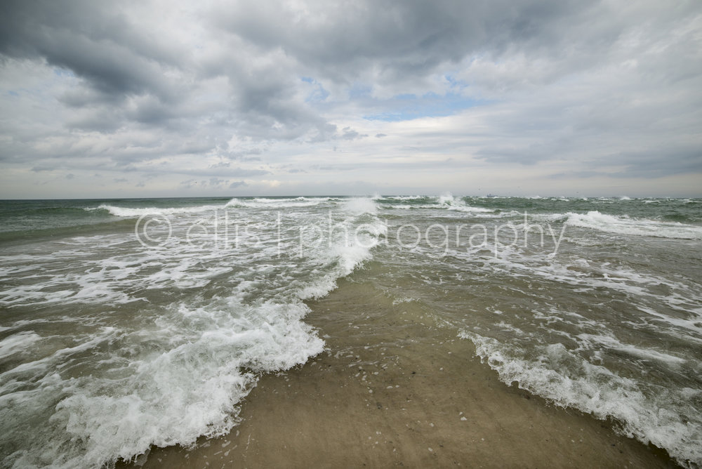 Where the north sea and the baltic sea kiss. Two seas meet each other. Dramatic sky. Skagen, the most northern part of Denmark. On the photo you see one sea is peaceful and the other one has big waves. Ellis Photography