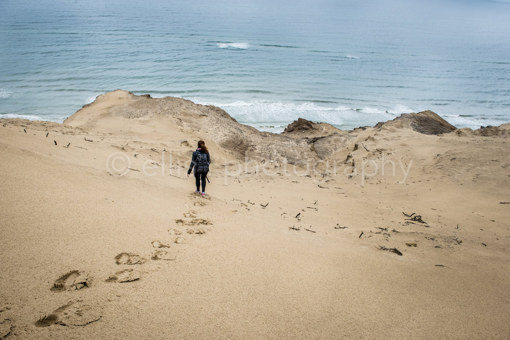 Woman with backpack walking down the dunes of Rubjerg fyr Denmark. Footprints in the sand. Walking towards the north sea. Travel photography.
