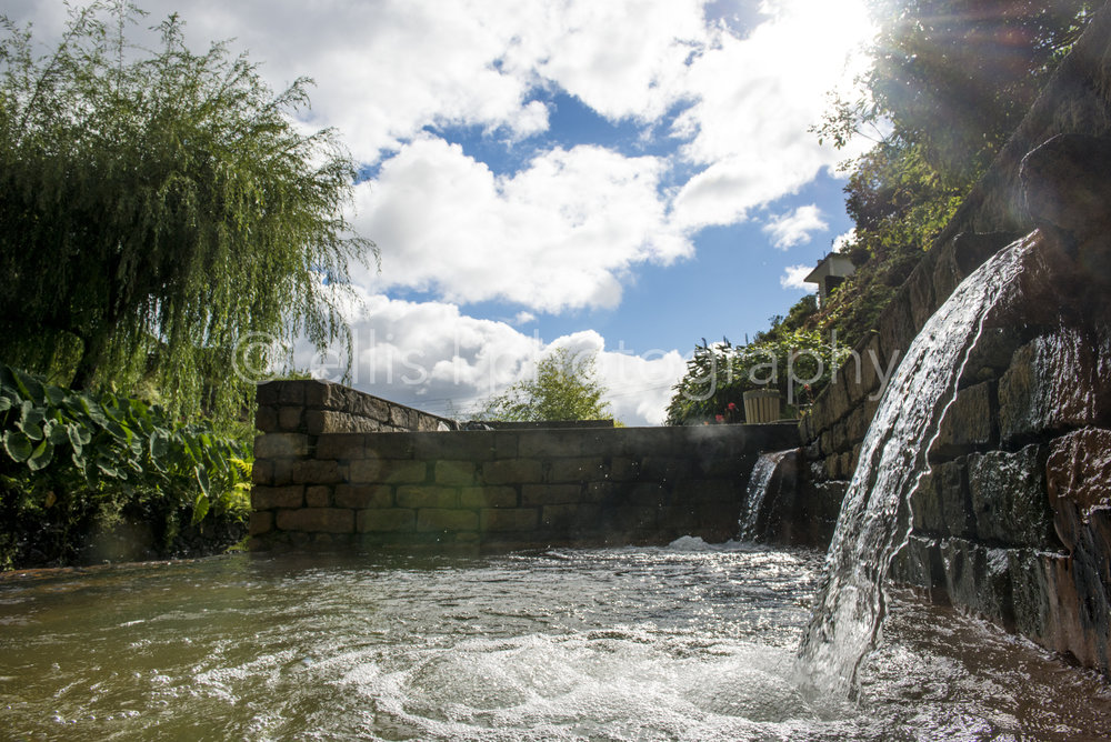Natural hot spring, Poca da Dona Beija, in Furnas, Sao Miguel. Sun coming through clouds and waterfall