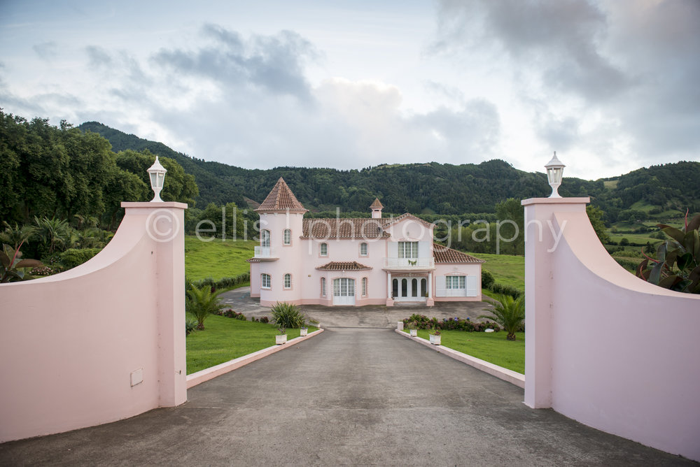 Pink house, barbie doll house on the green island of Sao Miguel in Faial da Terra. Mountains cover the house. Ellis Photography