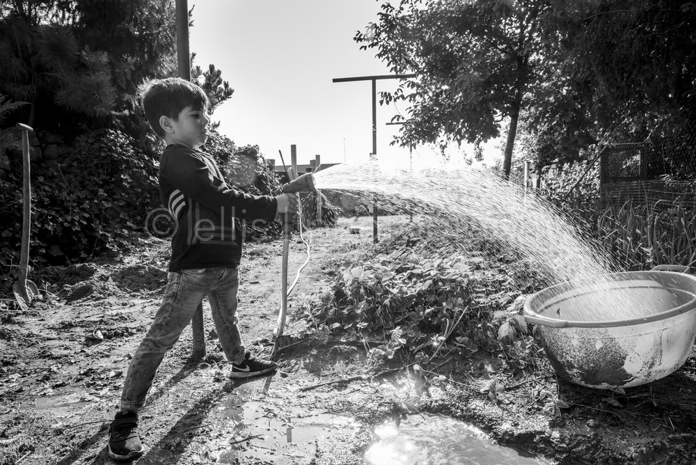 Daily life photo of a boy who is playing with a waterhose in the backyard. Black and white Ellis photography. Jongen is in de tuin aan het spelen met een waterslang.