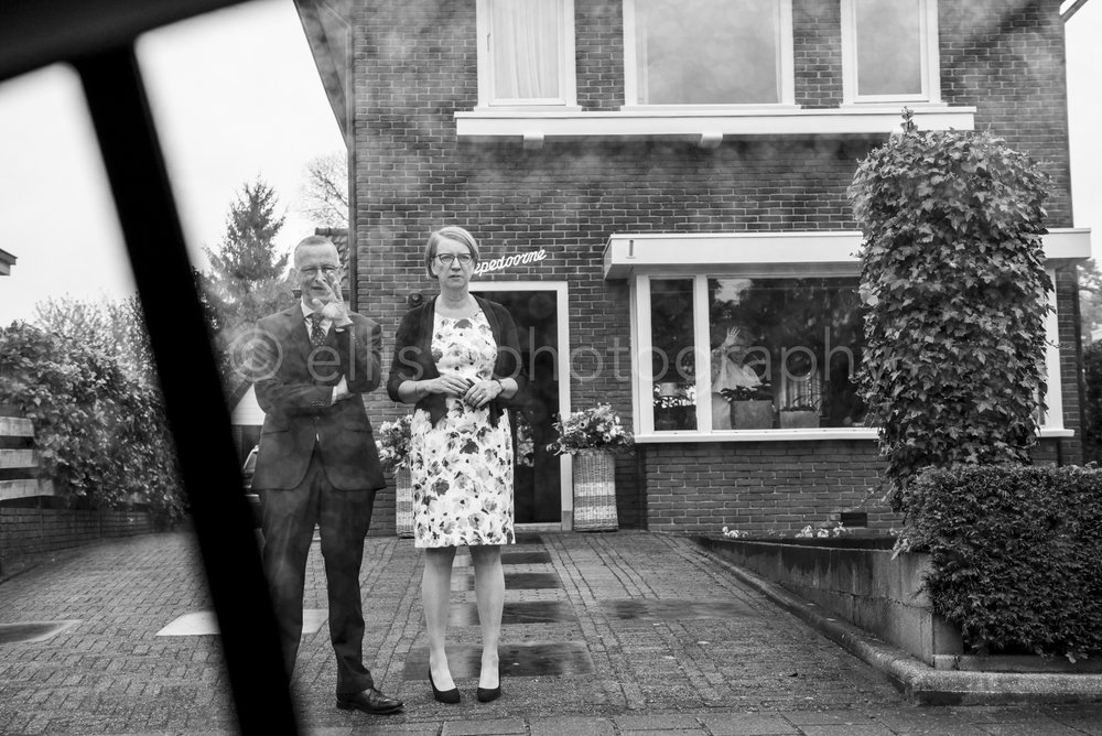 Daily life black and white photography. Partens of the bride waving their daughter and son in law goodby. Inside the house you see the mother of the groom waving. Little raindrops on the window of the car. Wedding daily life photography by Ellis Peeters Photography.