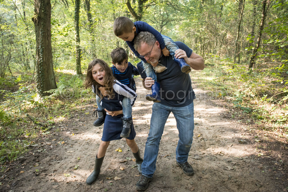 Opa is samen met zijn kleinkinderen naar het bos voor een middagje day in the life, ongedwongen, spontane daily life fotografie. Opa heeft jongste kleinzoon op de nek en kleindochter heeft haar broertje op de rug.