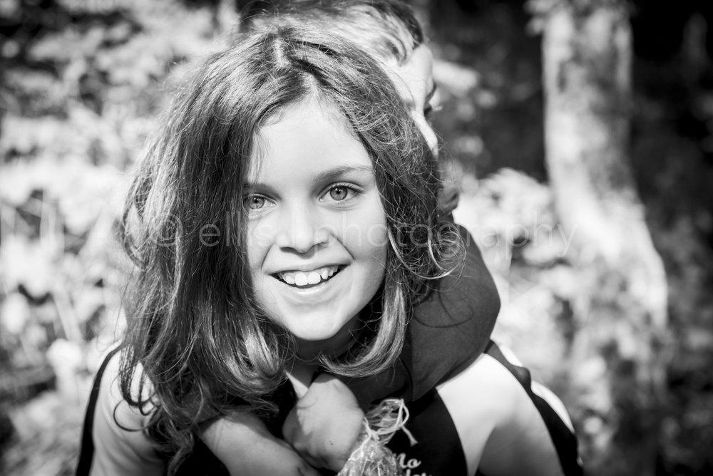 Mooie zwart wit portret van een meisje tijdens een day in the life familiefotografie in het bos. Mooie spontane lach.