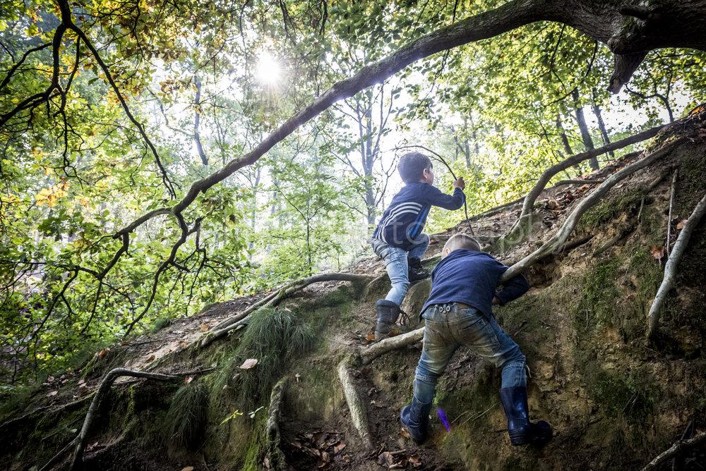 Twee broertjes zijn aan het klimmen in het bos, op de wortels van een boom. Ongedwongen, spontane day in the life foto's.