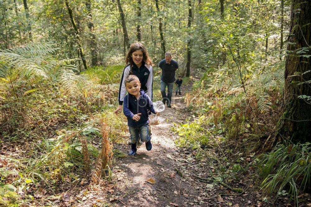 Day in the life familiefotografie. Opa loopt samen met zijn kleinkinderen in het bos. Jongste rent voorop de heuvel op op een klein pad. Fotograaf Ellis Peeters Photography.