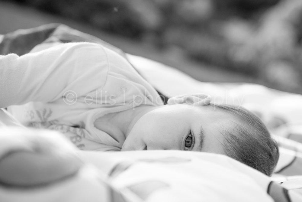 Baby, meisje ligt op de grond. Ongedwongen portret zwart wit foto. Ellis Peeters Photography.