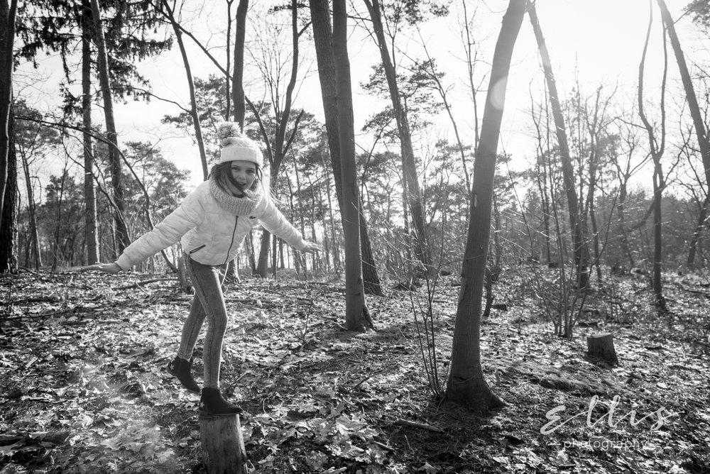 Meisje in het bos, balancerend op een boomstam. Zwart wit daily life foto genomen door Ellis photography.