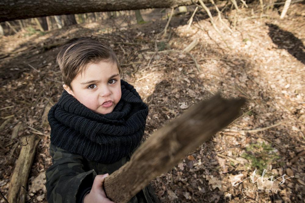 Jongetje wijst met een stok richting de camera. Bosrijke omgeving voor een ontspannen day in the life familie fotografie.