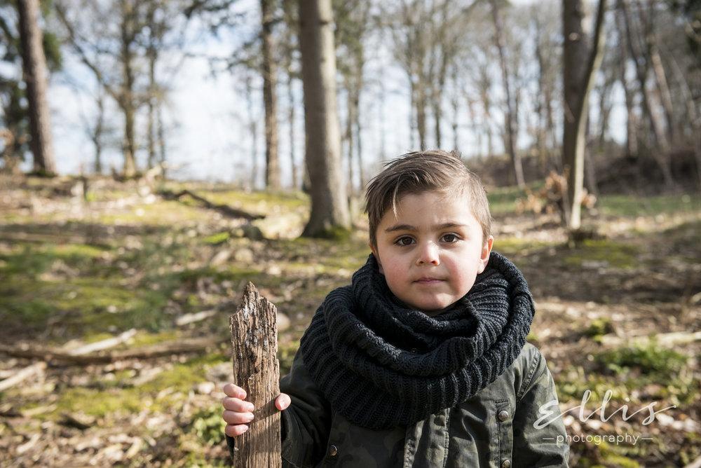 Portret van een jonge jonge met een stok in zijn hand. Kijkt bedenkelijk naar de camera. In het bos ongedwongen familie fotoshoot door Ellis Photography.
