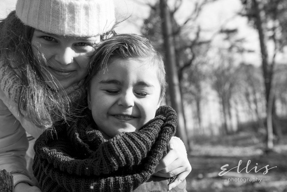 Zwart wit portret foto van een broertje en zusje in een bosrijke omgeving. Ontspannen en ongedwongen familie fotografie. Natuurlijk licht.